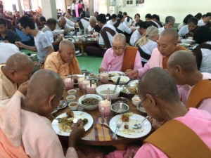 Burmese Nuns and Yogis in dinning hall mindfully eating their lunch in silence.